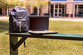 Various educational, learning objects on bench in front of a school building.  Items include:  backpack, laptop computer.  No people.
