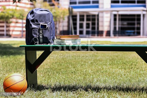 Various educational, learning objects on bench in front of a school building.  Items include:  backpack, textbooks, cell phone, earbuds, basketball.