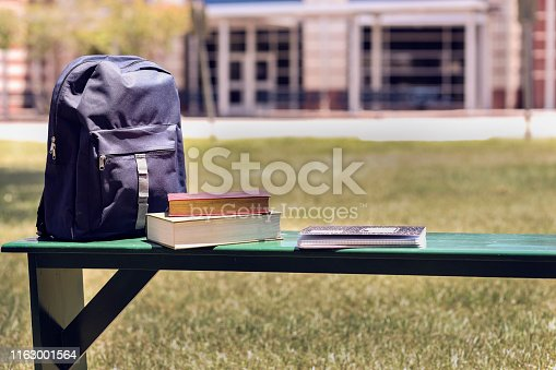Various educational, learning objects on bench in front of a school building.  Items include:  backpack, textbooks.