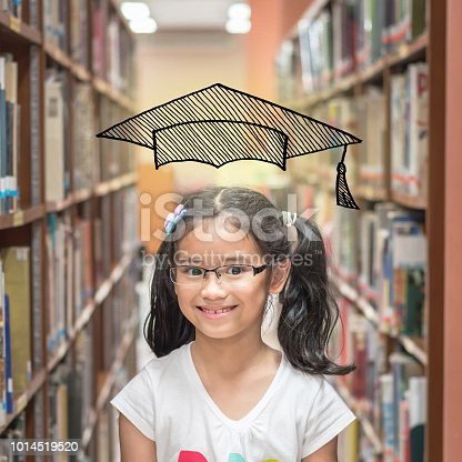 977488078 istock photo Educational success concept with smart school kid student with imaginary doodle graduation cap in library 1014519520