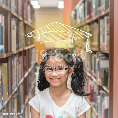 977488078 istock photo Educational success concept with smart school kid student with imaginary doodle graduation cap in library 1080198062