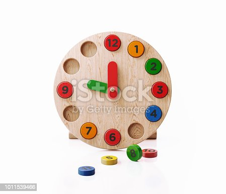 Educational wooden toy clock on white background. Horizontal composition with copy space.