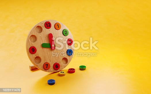 Educational wooden toy clock on yellow background. Horizontal composition with copy space.