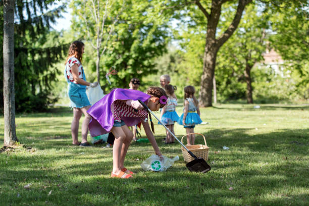 Educator and kids cleaning garbage from a park stock photo