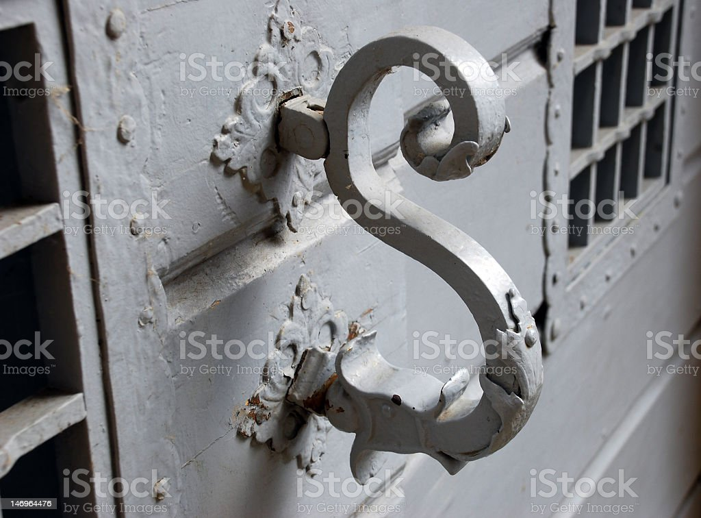 Eerie S-shaped door knocker stock photo