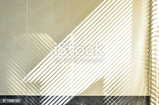 istock Effect on wall of sunlight through blind shutters. 911586162