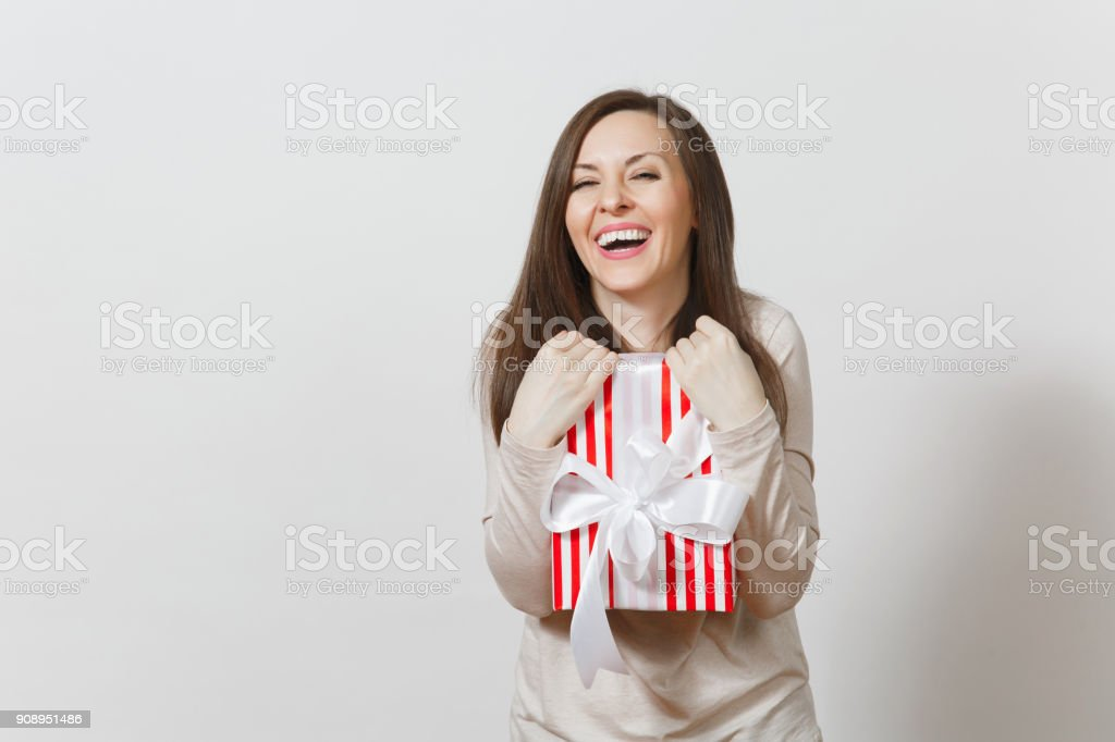 Effective woman hugging red striped present box with ribbon, bow isolated on white background. For advertisement. St. Valentine's Day, International Women's Day, Christmas, birthday, holiday concept. stock photo