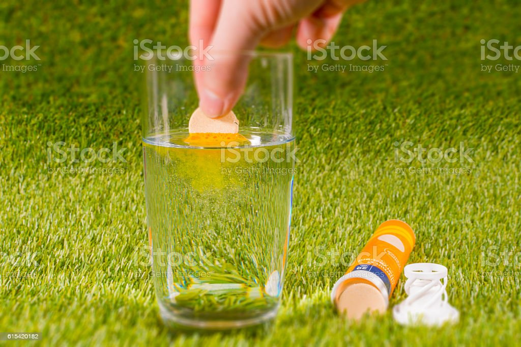 Effervescent Vitamin C Tablet fizzing in water stock photo