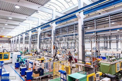 Color image of futuristic new factory producing plastic pieces for car industry. Factory modern interior where is placed a lot of robot machines which provide work for human, space for copy. Modern indoor hall for assembly. Large group of automated injection moulding machines for plastic parts production.