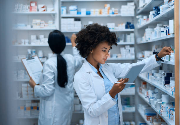 Efficient pharmacy operations thanks to teamwork Shot of a young woman doing inventory in a pharmacy on a digital tablet with her colleague in the background cure stock pictures, royalty-free photos & images