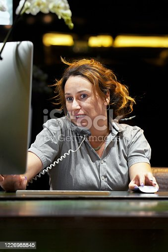 1167562098 istock photo Efficient secretary working in the office, she is answering phone calls. Customer service concept. Night time. 1226988845