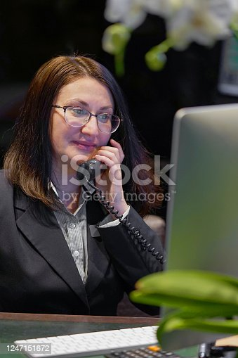 1167562098 istock photo Efficient secretary working in the office, she is answering phone calls. Customer service concept. Night time. 1247151672