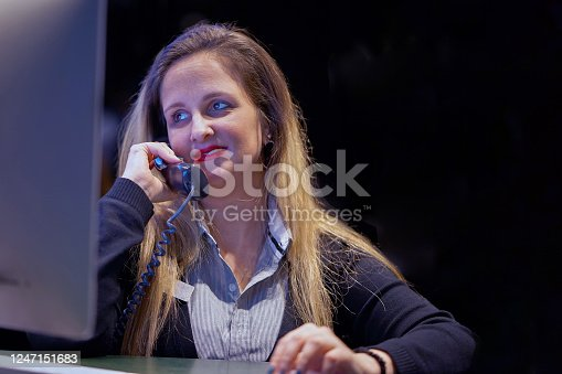 1167562098 istock photo Efficient secretary working in the office, she is answering phone calls. Customer service concept. Night time. 1247151683