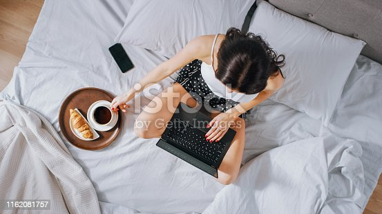 994789938 istock photo Efficient Young Millennial Girl Sitting on a Bed in the Morning, Uses Laptop Computer and Eats Croissants and Drinks Coffee for Breakfast. Top Down Shot. 1162081757