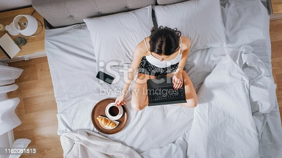 994789938 istock photo Efficient Young Millennial Girl Sitting on a Bed in the Morning, Uses Laptop Computer and Eats Croissants and Drinks Coffee for Breakfast. Top Down Shot. 1162081813