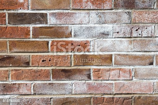 Image of powdered white efflorescence on a red brick wall.  The white dusty material is caused by moisture within the brick wall pushing salts to the surface.