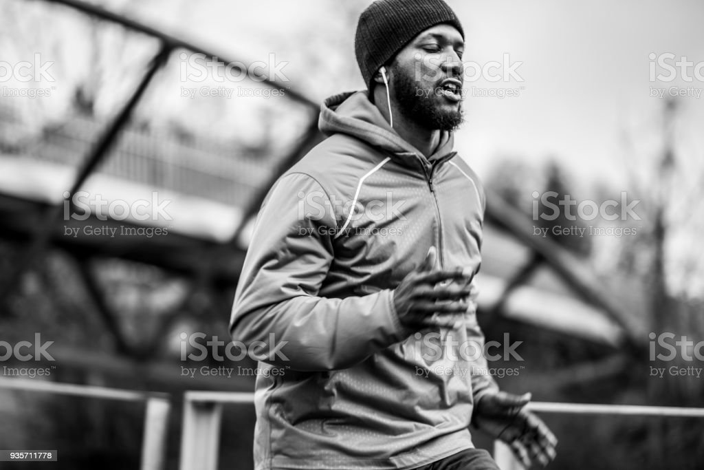Black and white image of African American man jogging on winter...