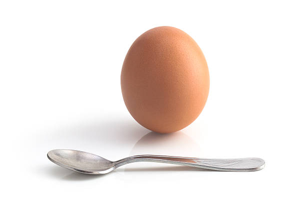 egg and spoon on white background stock photo