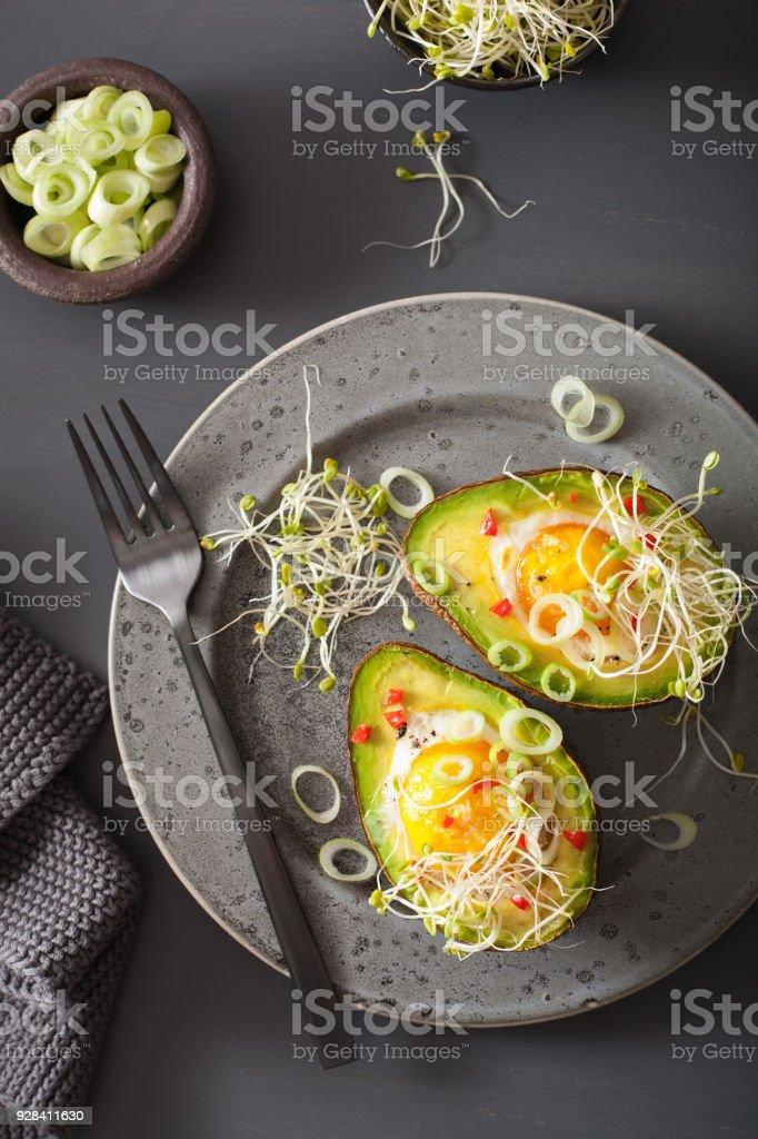 Ei in Avocado mit Frühlingszwiebeln und Alfalfa Sprossen gebacken – Foto