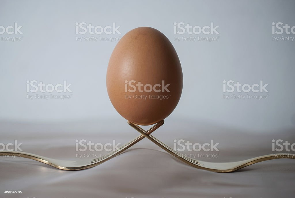 Egg balancing on two interlocking gold forks royalty-free stock photo