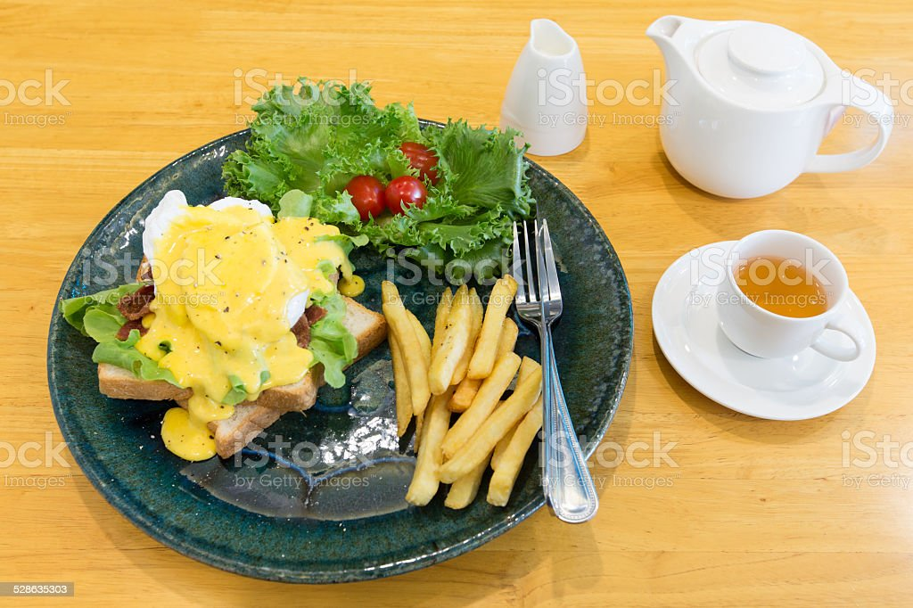 Egg Benedict serve with french fries and hot tea stock photo