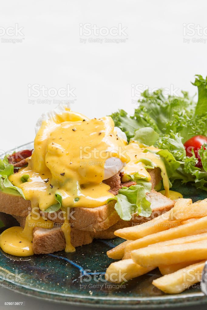 Egg Benedict with french fries stock photo