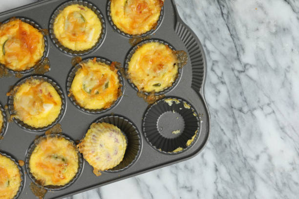 Egg Bites An  overhead close up horizontal photograph of a baking pan with freshly made egg bites, it appears the chef has already sampled one of them. muffin tin stock pictures, royalty-free photos & images