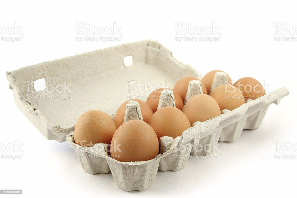 Egg box with 10 brown eggs on white surface stock photo