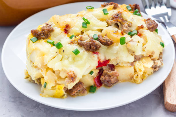 Egg casserole with potatoes, sausage and pepper, on white plate, horizontal stock photo