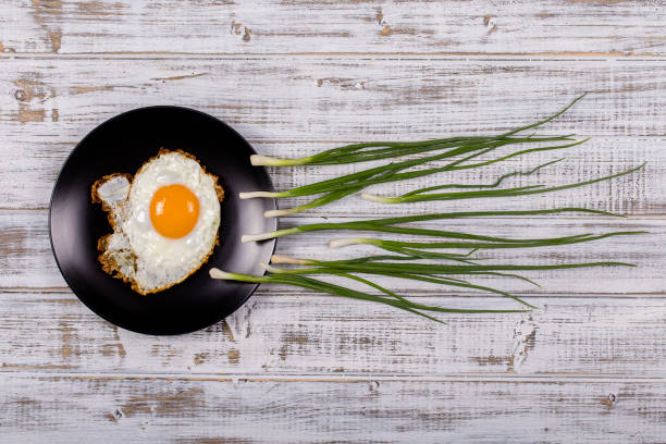 Egg , chives and black plate look like sperm competition, Spermatozoons floating to ovule in white wooden background stock photo