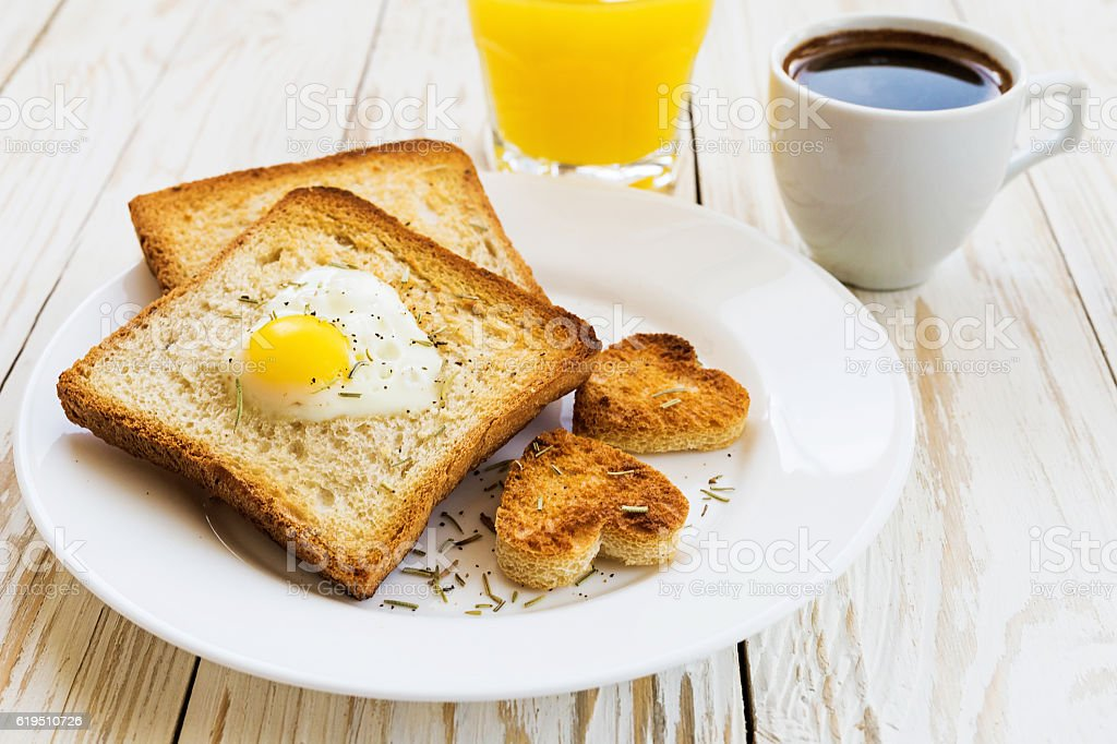 Egg fried in a heart-shaped toast cutout sprinkled – Foto