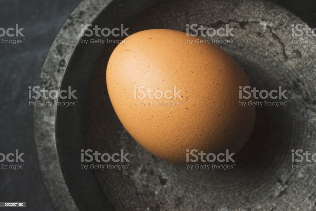 Egg in black marble bowl stock photo