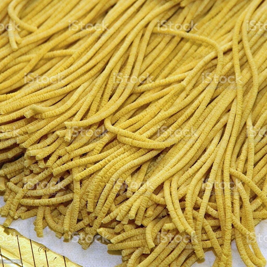 Gli spaghetti all'uovo kneaded a mano - foto stock