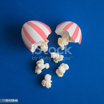 Popcorn out from broken egg minimal food and cinema creative concept.