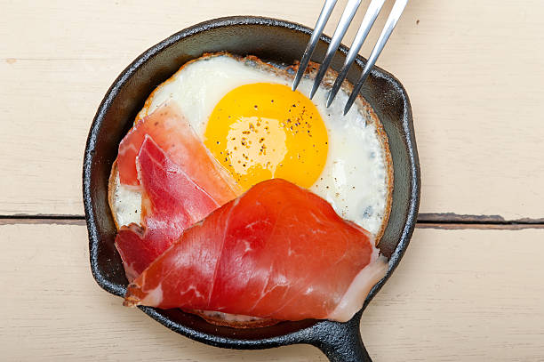 egg sunny side up with italian speck ham stock photo