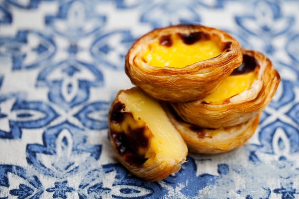 Egg tart, traditional Portuguese dessert, pastel de nata. Blue background. Close up. stock photo