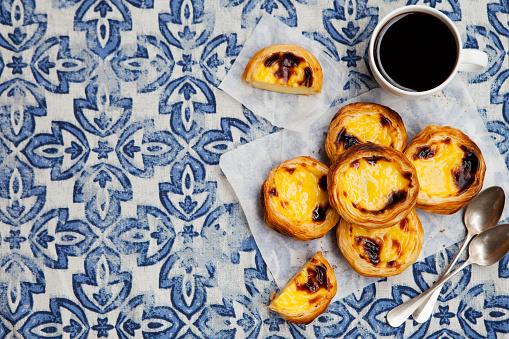 Egg tart, traditional Portuguese dessert, pastel de nata. Blue background. Top view. Copy space.