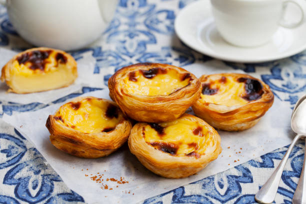 Egg tart, traditional Portuguese dessert, pastel de nata on a parchment paper. Blue background. stock photo
