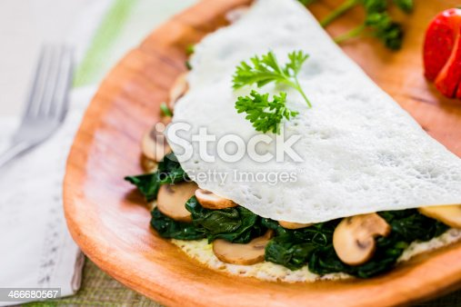 An egg-white omelet with sautéed spinach and sliced mushrooms.