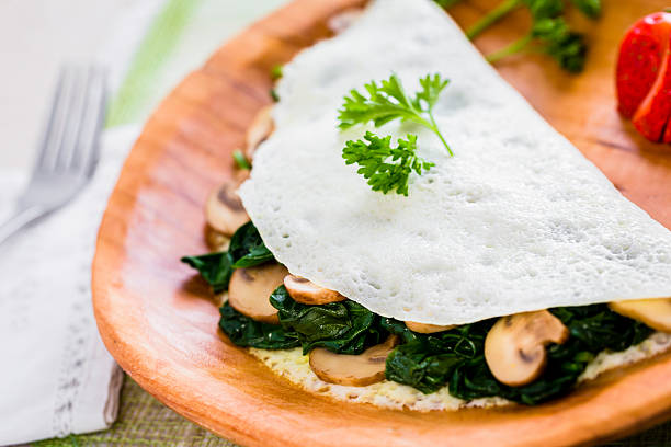 Egg White Omelet with Spinach and Mushrooms An egg-white omelet with sautéed spinach and sliced mushrooms. egg white stock pictures, royalty-free photos & images