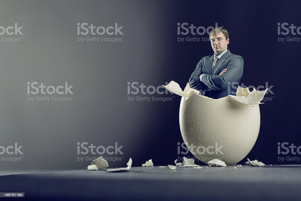 Egg with man inside isolated on gray background stock photo