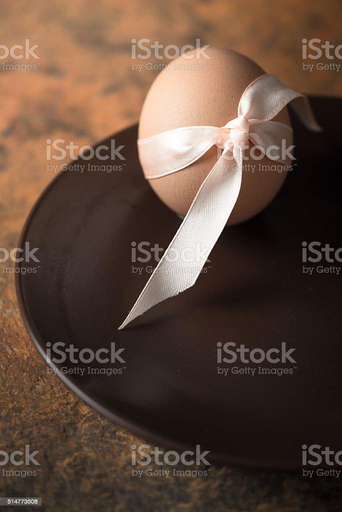 Ei mit Band auf der Braun Platte vertikal Lizenzfreies stock-foto