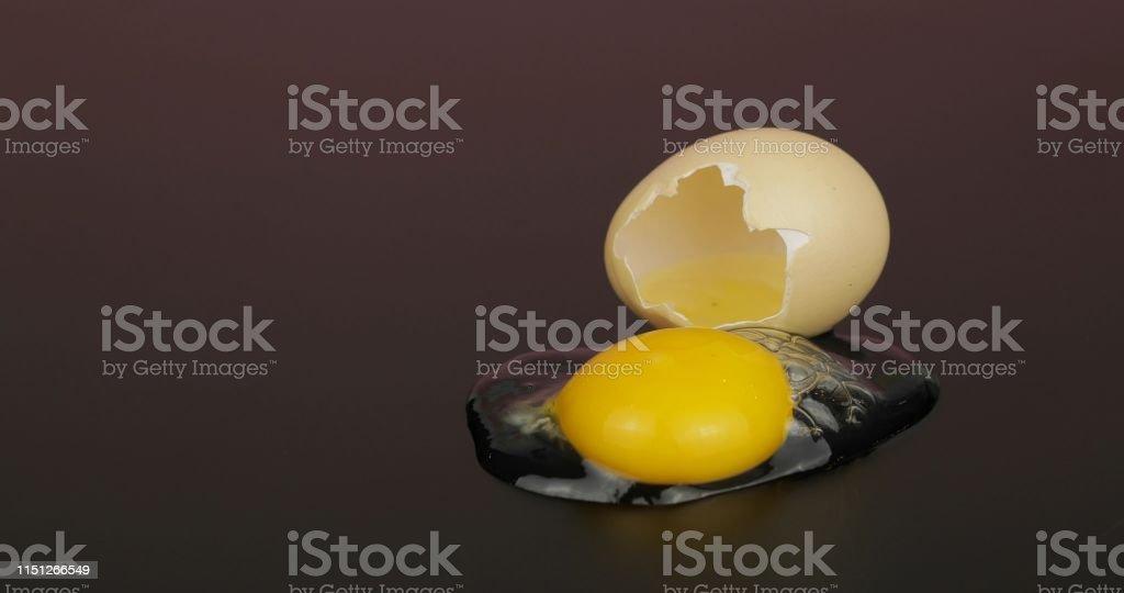 Egg yolk poured out from broken eggshell on black surface.