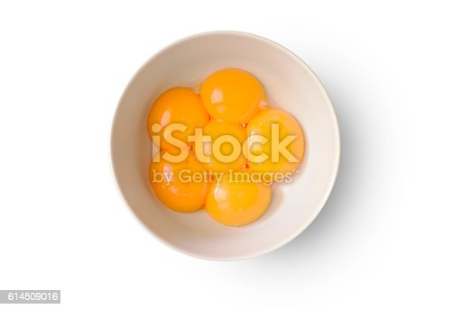 Six fresh and shiny yolks in a bowl on white background.