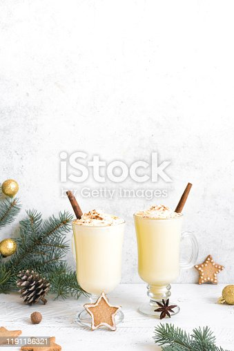 Eggnog Christmas drink with festive decor, gingerbread cookies and winter spices on white, copy space. Homemade eggnog for Christmas and winter holidays.