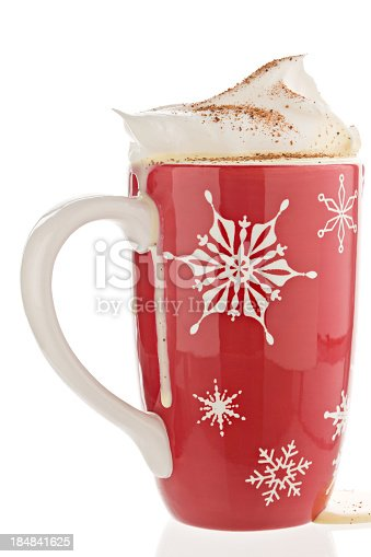 A close up of a red mug with white snowflakes filled to overflowing with eggnog, topped with whipped cream and sprinkled with ground nutmeg. Isolated on white.
