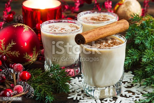 Eggnog with milk, rum, cinnamon and nutmeg in the glasses on the rustic wooden table with Christmas decoration.