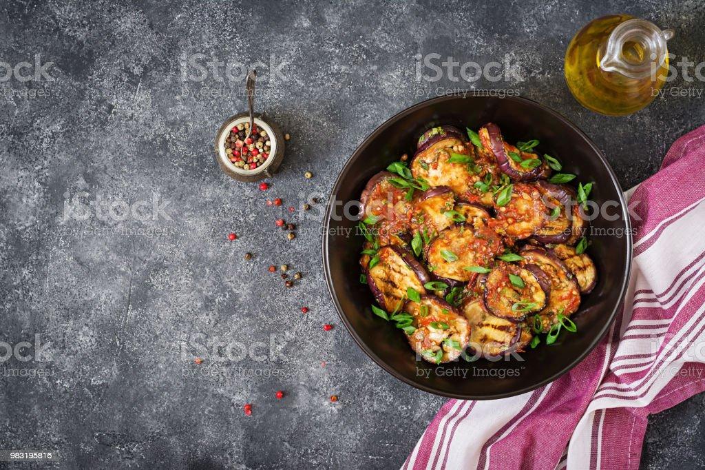 Auberginen gegrillt mit Tomatensauce, Knoblauch, Koriander und Minze. Veganes Essen. Gegrillte Aubergine. Ansicht von oben. Flach zu legen – Foto