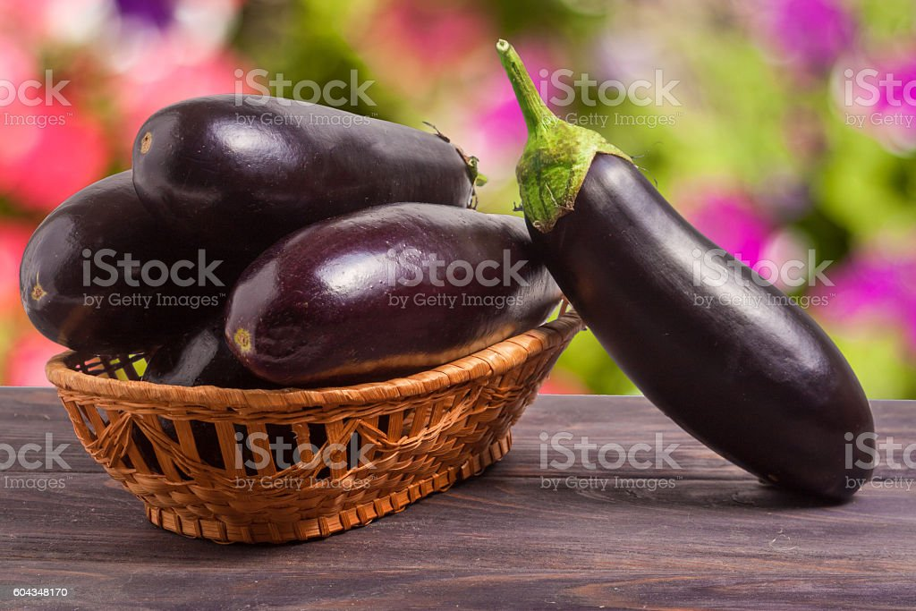 eggplant in a wicker basket on wooden table with blurred - Photo