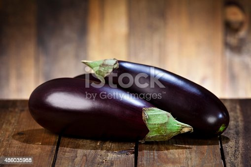 Still life of two ripe eggplants on a rustic wood table.  Predominant colors are brown and purple. DSRL studio photo taken with Canon EOS 5D Mk II and Canon EF 70-200mm f/2.8L IS II USM Telephoto Zoom Lens
